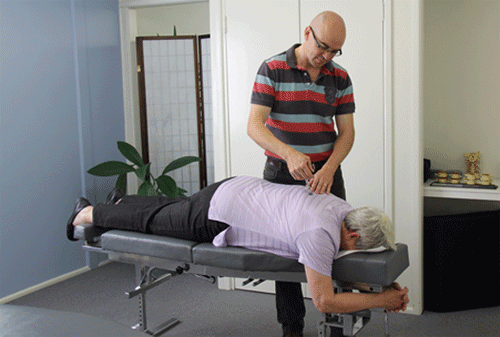 Chiropractor Dr David Malone using the Activator to adjust a client